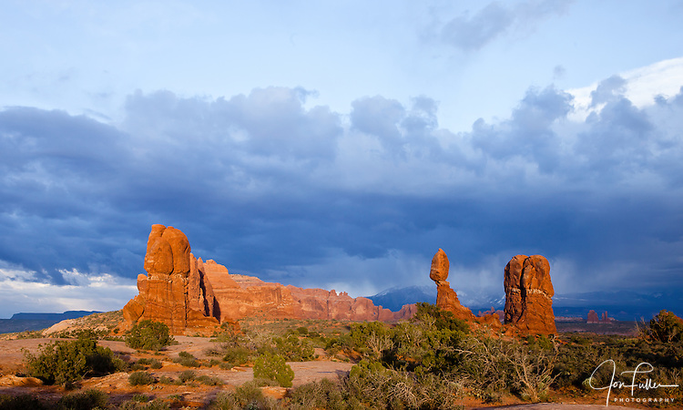 Balanced Rock in Arches National Park near Moab, Utah, USA at sunset with stormy clouds and snow on the La Sal Mountains.