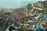 A man scavenges for recyclable items in the smoldering municipal garbage dump in Chennai, India.