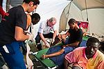 René, médecin français de l'ONG DASUD 62, examine un blessé dans le Poste Médical Avancé installé dans le camp de réfugiés de Jacmel le 21/01/2010. Plusieurs milliers de personnes dont les maisons ont été détruites par le séisme du 12/01/2010 se trouvent rassemblées dans le stade de football.