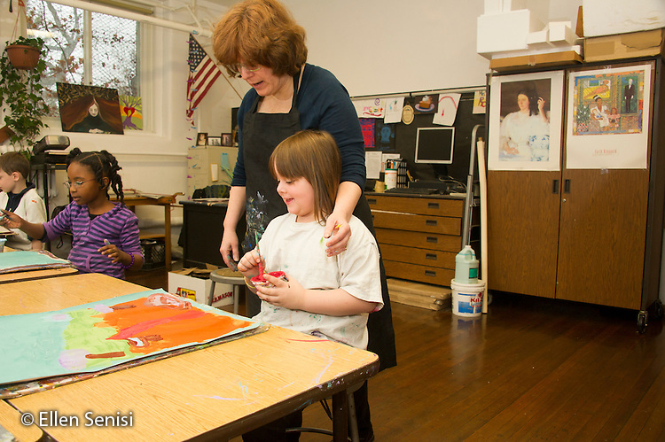 MR / Schenectady, New York. Yates Arts-in-Education Magnet School (urban public school). First grade classroom. Art teacher compliments student (girl, 7) on the painting she made during art class. MR: Jol1, Sco1. ID: AM-g1w. © Ellen B. Senisi.