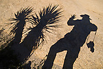 My shadow with yucca tree against quartz-monzanite rock, Belle Campground, Joshua Tree National Park, Calif.