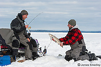 Anglers holding a whitefish caught ice fishing in winter.
