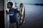 LUKUTU, DEMOCRATIC REPUBLIC OF CONGO MARCH 13: A boy holds a dead monkey on a boat on March 13, 2006 outside Lukutu, Congo, DRC. The monkey was bought by the boat?s captain. Congo River is a lifeline for millions of people, who depend on it for transport and trade. During the Mobuto era, big boats run by the state company ONATRA dominated the traffic on the river. These boats had cabins and restaurants etc. All the boats are now private and are mainly barges that transport goods. The crews sell tickets to passengers who travel in very bad conditions, mixing passengers with animals, goods and only about two toilets for five hundred passengers. The conditions on the boats often resemble conditions in a refugee camp. Congo is planning to hold general elections by July 2006, the first democratic elections in forty years. (Photo by Per-Anders Pettersson)
