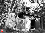 "This 1995 photo depicts Mieke Crider, artist and Russian Village resident, holding one of her works ""Archangel Michael""."