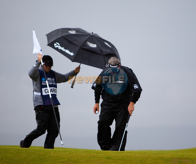 Darren Clarke and his caddie dash for shelter during the first days play of the Barclays Scottish Open, played over the links at Castle Stuart, Inverness, Scotland from 7th to 10th July 2011:  Picture Stuart Adams /www.golffile.ie  7th July July 2011