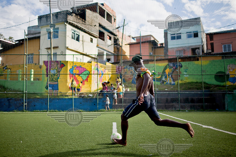 A man plays football (soccer) on an artificial pitch in the Tavares Basto favela.