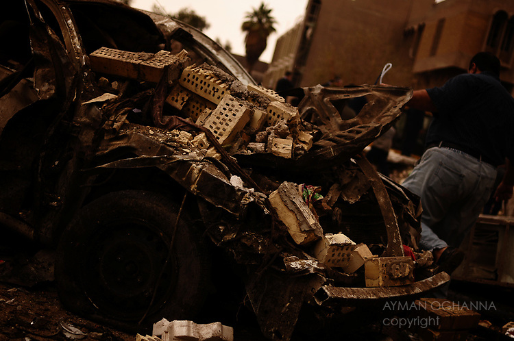 Baghdad, Iraq  : Tues 8th Dec 2009 :..An Iraqi man passes the burned out shell of a car outside Iraq's Interior Justice Ministry ..Devastating bomb attacks killed at least 112 in the Iraqi capital on Tuesday morning..Ayman Oghanna For The Times