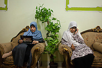 Two Muslim sisters, Dr Kamel (left) and Dr Heba (right) , rest before lunch at a meeting with women in the rural village of Al Saf, in the South of Cairo. Dr Omaima's laptop is covered with a campaign sticker for Dr Mohamed Morsi, chairman and Presidential candidate for the Freedom and Justice Party, a political party founded by the Muslim Brotherhood. Al Saf village, Egypt. June 2012
