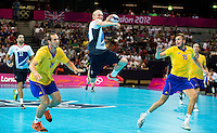 31 JUL 2012 - LONDON, GBR - Sebastien Edgar (GBR) of Great Britain (centre, in white, blue and red) shoots during the men's London 2012 Olympic Games Preliminary round handball match against Sweden at The Copper Box in the Olympic Park, in Stratford, London, Great Britain (PHOTO (C) 2012 NIGEL FARROW)