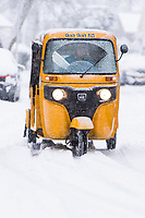 A yellow tuk tuk in the snow in the village of Redbourn, Hertfordshire, UK. Sunday 10 December 2017.