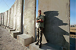 A Palestinian man stands next  to concrete barricades part of the construction of the new security fence in the Arab east Jerusalem suburb of Sawahreh from Jerusalem, as he waits for a taxi, September 29, 2003. Photo by Quique Kierszenbaum