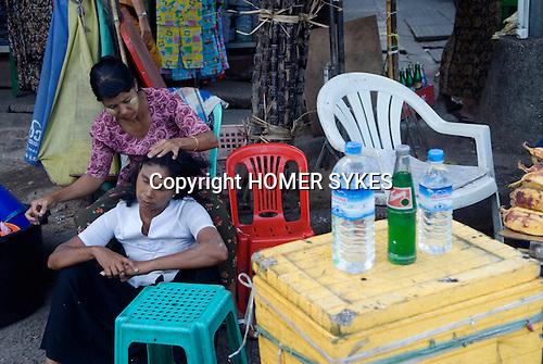 Yangon Myanmar (Rangoon Burma) 2008. Woman removing hair lice from another woman head hair.