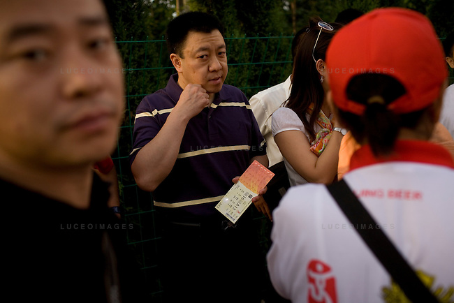 Locals try to scalp tickets near the Olympic Green zone in Beijing, China on Saturday, August 16, 2008.  Most scalpers are asking more than three times the retail value of the ticket. Kevin German
