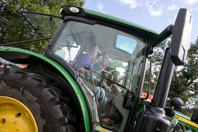 iowapol15_111_081815_dragoUNITED STATES - August 17: Republican presidential candidate and Ohio Governor John Kasich rides a John Deere tractor down the concourse at the Iowa State Fair on Tuesday, August 18, 2015 in Des Moines, Iowa. (Photo By Al Drago/CQ Roll Call)