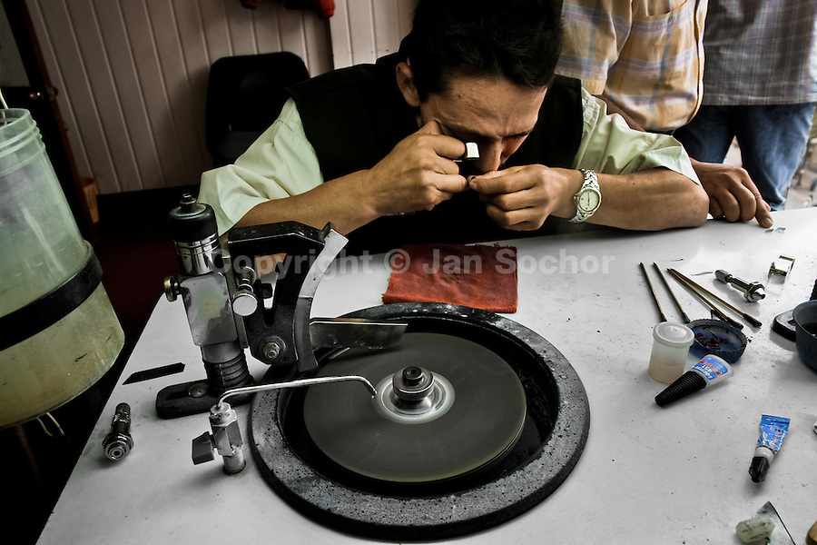 An emerald cutter looks through a magnifying lens at a gemstone he is working on in a cutting and polishing workshop in Bogota, Colombia, 31 March 2006. Approximately 60 percent of the world's total amount of emeralds come from Colombia. Most of the rough gems are processed in workshops located in the emerald district in downtown Bogota. Due to their special clarity and deep vivid green color, Colombian gemstones are considered the most beautiful emeralds in the world.