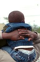 Son age 3 riding on fathers shoulders age 25 at Cinco de Mayo.  St Paul  Minnesota USA