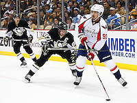 Marcus Johansson #90 of the Washington Capitals skates with the puck in front of Sidney Crosby #87 of the Pittsburgh Penguins in the first period during the game at Consol Energy Center in Pittsburgh, Pennsylvania on December 14, 2015. (Photo by Jared Wickerham / DKPS)