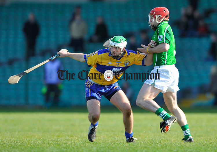 Clare's Tommy Holland tries to get away frpm Limerick's Andrew O Shaughnessy during their National League game in Limerick. Photograph by John Kelly.