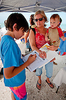 """It's not much, but I feel like I have to do something to save the ocean,"" says twelve-year-old Dalton Patrick as he signs a petition while his grandmother, Christine Capps and cousin Jack Capps watch before joining hands at noon for fifteen minutes during Hands Across the Sands at Bonita Beach, Florida. June 26, 2010.  Photo by Debi Pittman Wilkey"