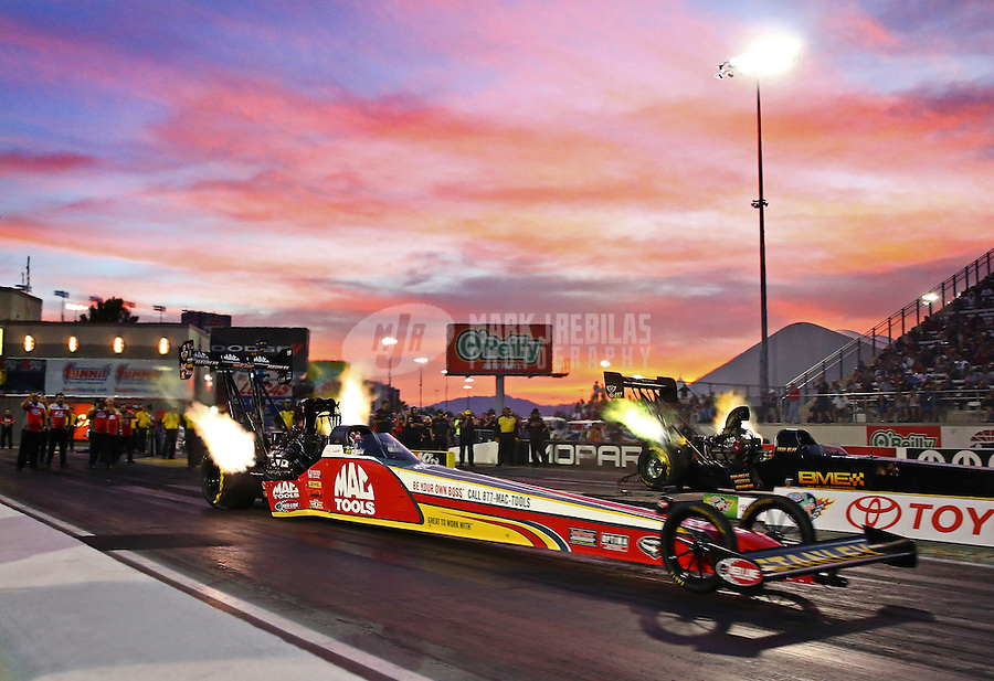 Oct 31, 2014; Las Vegas, NV, USA; NHRA top fuel driver Doug Kalitta (near) races alongside Troy Buff during qualifying for the Toyota Nationals at The Strip at Las Vegas Motor Speedway. Mandatory Credit: Mark J. Rebilas-USA TODAY Sports