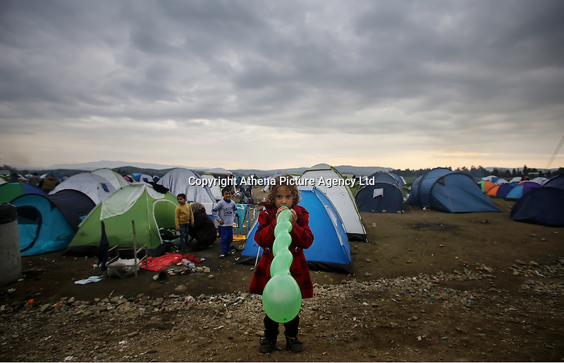 Pictured: A young girl plays with a balloon at the Idomeni camp Monday 29 February 2016<br /> Re: A crowd of migrants has burst through a barbed-wire fence on the FYRO Macedonia-Greece border using a steel pole as a battering ram.<br /> TV footage showed migrants pushing against the fence at Idomeni, ripping away barbed wire, as FYRO Macedonian police let off tear gas to force them away.<br /> A section of fence was smashed open with the battering ram. It is not clear how many migrants got through.<br /> Many of those trying to reach northern Europe are Syrian and Iraqi refugees.<br /> About 6,500 people are stuck on the Greek side of the border, as FYRO Macedonia is letting very few in. Many have been camping in squalid conditions for a week or more, with little food or medical help.