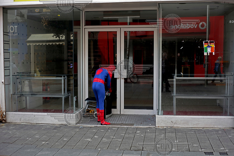 A person dressed as Spiderman stands in the doorway of a shop on Henry Street.