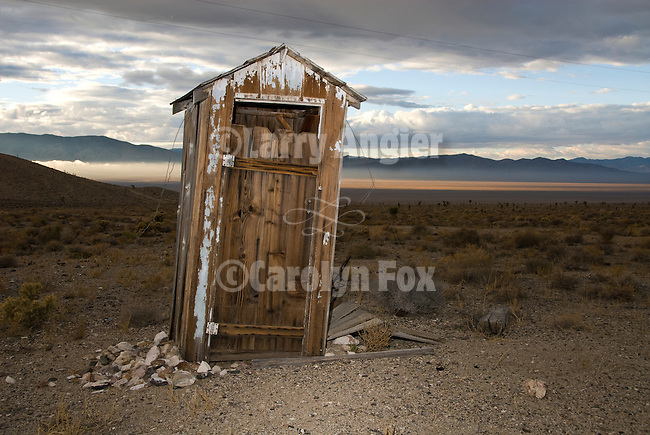 Tied-down leaning weathering wooden outhouse at a ghost tow in Nevada