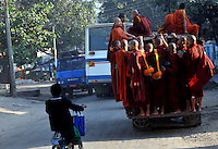 Monks ride a bus, early morning, on the way to beg for food from villagers in Mandalay, Burma Oct 08.  Monks in this largely Buddhist country have to beg from villagers in order to feed themselves and in this city the government hand-outs stopped after the &quot;saffron revolution&quot; of October 2007.<br />
