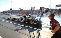 May 31, 2013; Englishtown, NJ, USA: A crew member runs alongside the NHRA top fuel dragster driver Shawn Langdon doing a burnout during qualifying for the Summer Nationals at Raceway Park. Mandatory Credit: Mark J. Rebilas-
