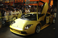 Visitors look at a Lamborghini at the Auto China 2004 exhibition in Beijing, China..