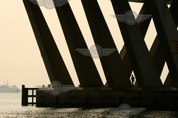 Man fishing from the support of a bridge over the mouth of the Singapore River.