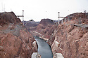 Photo taken from the middle of Hoover Dam looking out at bypass bridge construction. Traffic currently travels on a two lane road over Hoover Dam which causes traffic congested and poses a security risk. Large trucks are not allowed over the dam and must make a major detour around the area. To deal with these problems the US 93 Highway, Hoover Dam Bypass project was developed approximately 1,500 feet downstream of the dam. It consists of 3.5 miles of roadway, two lanes in each direction, with a 1,900 foot long twin-rib concrete arch bridge 880 feet above the Colorado River's Black Canyon. It will be the longest concrete arch in the US and the 5th longest in the world. It will involve 60,000 cubic yards of concrete, 8,000 tons of steel, over 3.5 million cubic yards of earthwork excavation/embankment, and cost approximately $240 million.* Construction began in 2005 and is expected to be completed in 2010. US 93 is on the North American Free Trade Agreement (NAFTA) route between Mexico and Canada, and it is also the major commercial route between the states of Arizona, Nevada, and Utah. Photo taken February 2009..*Statistics source: Central Federal Lands Highway Division of the U.S. Department of Transportation's Federal Highway Administration, the lead managers of the project.