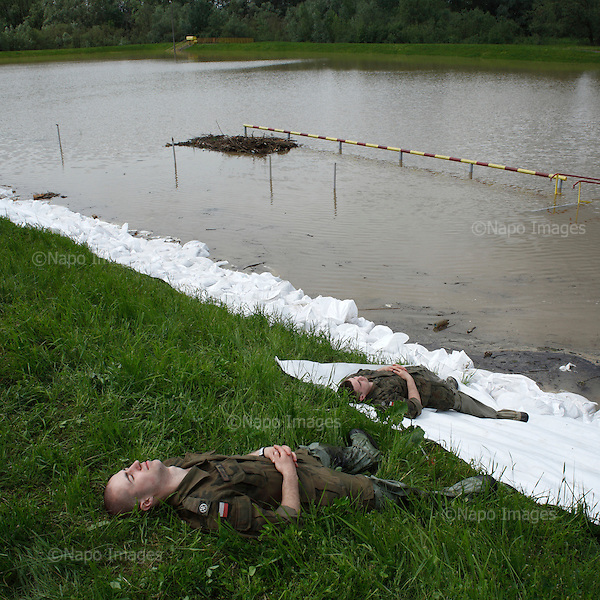 DOBRZYKOW, POLAND, MAY 24, 2010:.Polish soldiers taking a break at during building of the anti flood wall..The latest chapter of disastrous floods in Poland has been opened yesterday, May 23, 2010, after Vistula river broke its banks and flooded over 25 villages causing evacualtion of most inhabitants..Photo by Piotr Malecki / Napo Images..DOBRZYKOW, POLSKA, 24/05/2010:.Zolnieze robia sobie przerwe w budowaniu walu z workow z piaskiem.  Najnowszy akt straszliwych tegorocznych powodzi zostal rozpoczety wczoraj gdy Wisla przerwala waly na wysokosci wsi Swiniary kolo Plocka..Fot: Piotr Malecki / Napo Images ..