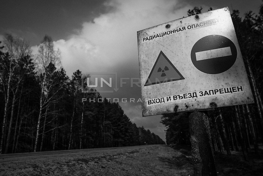 "Road sign through exclusion zone marked with signs that read  ""Radioactive danger. No trespassing"".  Local people say that there are less and less signs left every year because government wants to use previously closed territories."