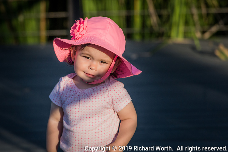 A toddler in a pink hat visiting an urban park on a fall afternooon.
