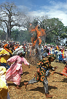 Women, dressed in their finest clothes, run around a small hut that has been set alight during the Makunduchi fighting festival. As the flames engulfed the hut a man, who had been waiting inside, jumps out to signify that no-one would die in a house fire in the coming year. Zanzibar, Tanzania, Africa. July 1997