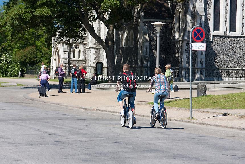 Bicyclist and pedestrian tourists near St. Alban's Church in Copenhagen, Denmark.