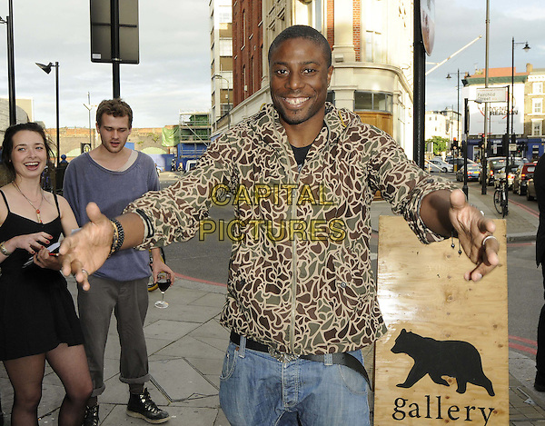 Leo Ihenacho.The 'Legends, An Exhibition of Portraits' private view, The Great Eastern Bear Gallery, Great Eastern St., London, England..August 2nd, 2012.half length green brown beige camouflage print jacket hands arms.CAP/CAN.©Can Nguyen/Capital Pictures.