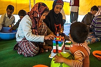 Children from flood affected families play and study in the Child-Friendly Space in Purnishadashah village, Jammu and Kashmir, India, on 24th March 2015. Save the Children has set up Child-Friendly Spaces (CFS) in many of the affected villages, providing a tented area where children can take emotional shelter and receive psychological first aid as well as continue their education as their homes and schools are being rebuild. Photo by Suzanne Lee for Save the Children