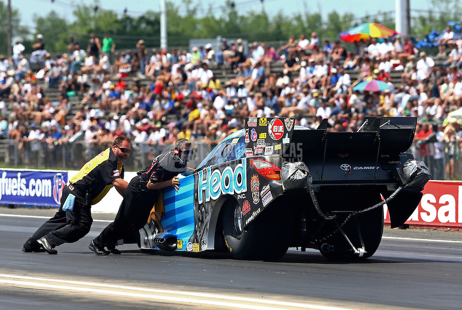 Jun. 2, 2013; Englishtown, NJ, USA: NHRA safety safari member and a crew member attempt to push the car of funny car driver Chad Head back to the starting line during the Summer Nationals at Raceway Park. Mandatory Credit: Mark J. Rebilas-
