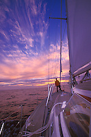 Man watching sunset at sea aboard sailing yacht 'Heron', Atlantic Crossing, off the Canary Islands, Spain
