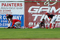 Batavia Muckdogs Mike Petrarca looks over outfielders Victor Encarnacion #6 (on back) and Roberto Reyes #4 (on stomach) after they collided on a fly ball, Romulo Ruiz #23 (far left) and David Medina #44 (far right) look on, during the second game of a doubleheader against the Mahoning Valley Scrappers at Dwyer Stadium on August 22, 2011 in Batavia, New York.  Reyes left the game and Mahoning Valley defeated Batavia 11-3.  (Mike Janes/Four Seam Images)