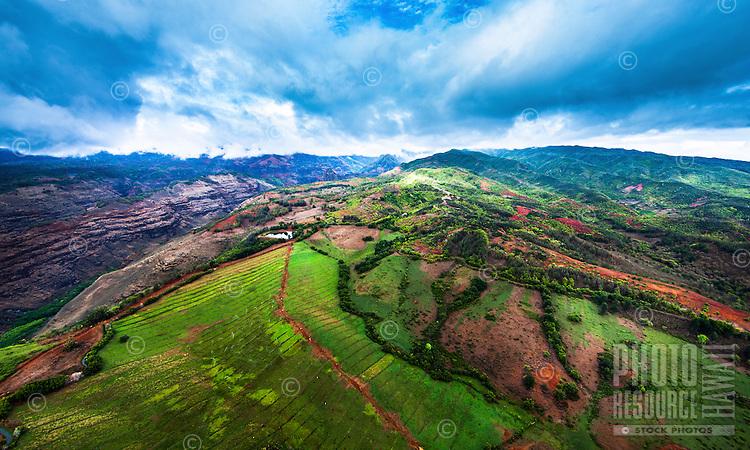 Green fields lead to Waimea Canyon while clouds streak over distant mountains on Kaua'i.
