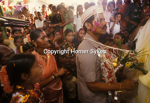 Hindu village wedding. The groom surrounded by local women stands one side of a symbol divide, a sheet, the bride is on the other side. The sheet is about to be pulled away lifted into the air and the couple will be united in marriage. Elephanta island off the coast of Bombay India.