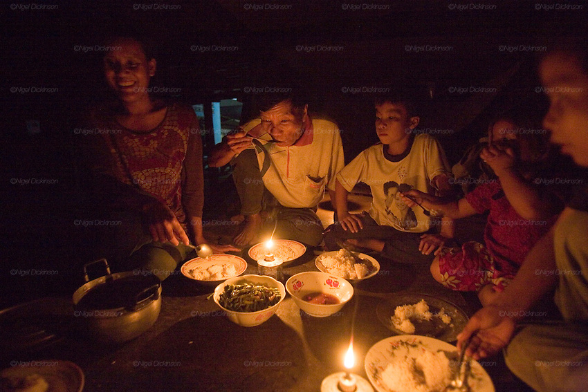 Sarak's family eating supper under candlelight. They have no electricity at their home..Sarak is a young Khmer boy who comes from a peasant family, living in a small village in Battambang Province, in northwest Cambodia. He lives with his mother and father, brothers, sister, cousins and his aunts and uncles. they are a big family. Sarak loves to learn how to be an acrobat in the local circus school, and spends as much time as he can doing headstands and somersaults with his friends. To be honest, he is a bit of a scoundrel, and enjoys head butting the billy goat, but he makes up by feeding all the animals in his parents little farm. His mother works at the fishmarket in Battambang town, whilst his father sells icecreams. They don't have very much money, not even electricity, so he and his brothers and sisters do their homework under candlelight. He likes to take trips, with his mother and cousins, on his uncle's scooter.