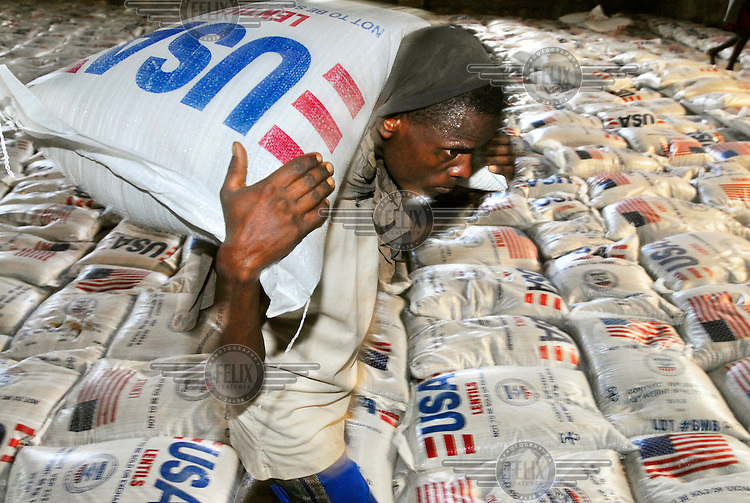 A man carries a sack of lentils donated by the USA in a food aid distribution warehouse run by the United Nations World Food Programme (UN WFP).  A severe drought has extended across East Africa after the rainy season which was expected in October 2005 failed to arrive. Levels of rainfall in the region have been far below normal putting millions of lives at risk..