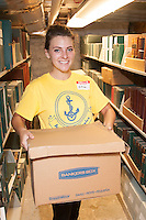 Jillian Brooks-Duval,'20, helps moves boxes of magazines and books to a storage area in the basement of the Redwood Library in Newport as he and other freshmen take part in Salve's Exploration Day of Service.