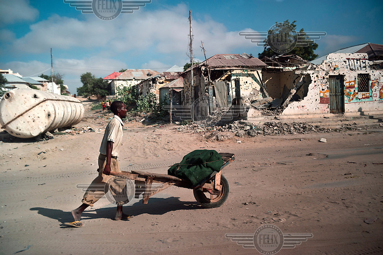 A man pushes a wheelbarrow past destroyed buildings, a result of 21 years of civil war, in Mogadishu.