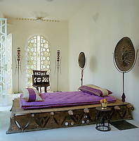 Ethiopian shields stand sentinel either side of a carved platform bed in this simply furnished guest bedroom