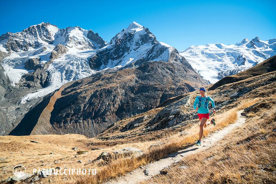 Trail running above the Rosegtal with Piz Bernina and Piz Roseg in the background. Pontresina, Switzerland